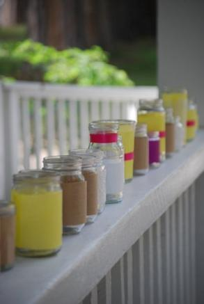 "100 recycled glass ""mason"" style jars that the bride collected for over 1 year. They all vary in size, and have been embellished with decorative papers and ribbons."